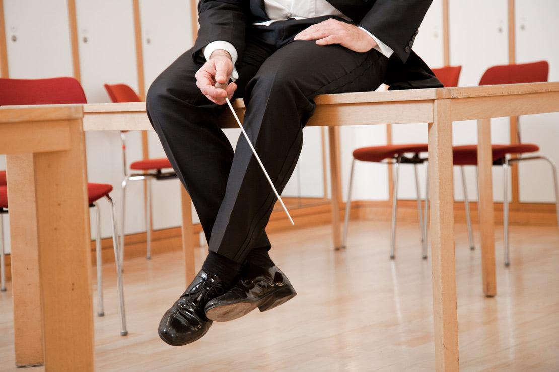 catrin_moritz_guerzenich_orchester_1, dirigend, dirigentenstab, lackschuh, frack, sitz auf dem tisch, kein kopf